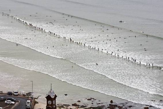 Pictured: A total of 93 surfers ride the same wave at the Earthwave Beach Festival at Surfer's Corner in Muizenberg on Sunday. The Guinness World Record of 110 surfers on the same wave was during the 2009 Earthwave event at the same venue. Photo: Lee Slabber