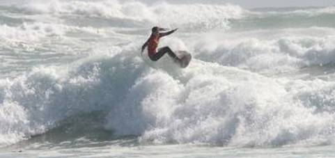Tanika Hoffman floats over the whitewater in the wild surf at Long Beach on her way to victory in the U16 division of the Women's Day Surf Challenge in Cape Town Photo courtesy Surfing South Africa