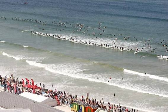 Pictured: Spectators lined the beach as 443 surfers paddled out and set a new Guinness World Record of 110 riding the same wave at the Earthwave Beach Festival at Muizenberg last year. Photo: Lee Slabber