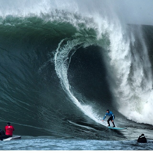Grant Baker (Durban, South Africa) shows poise under the lip of a giant wave during his Round 1 heat win in the Body Glove Mavericks Invitational in California on Friday  Credit: Grant Ellis / Surfer Mag
